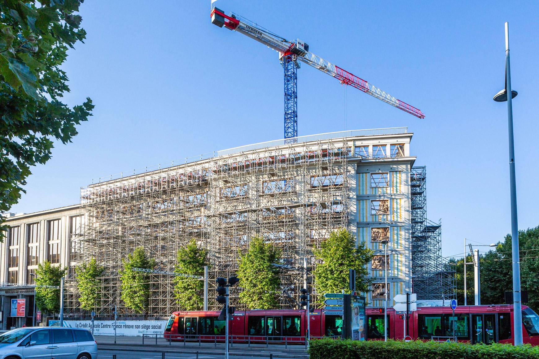 Réhabilitation lourde du siège sociale du Crédit Agricole Centre France à Clermont-Ferrand, labélisé BREEAM EXCELLENT, réalisé par le pôle Tertiaire de l'agence d'architecture SOHO ATLAS IN FINE LYON. Photo de chantier, vue sur la façade reprise.