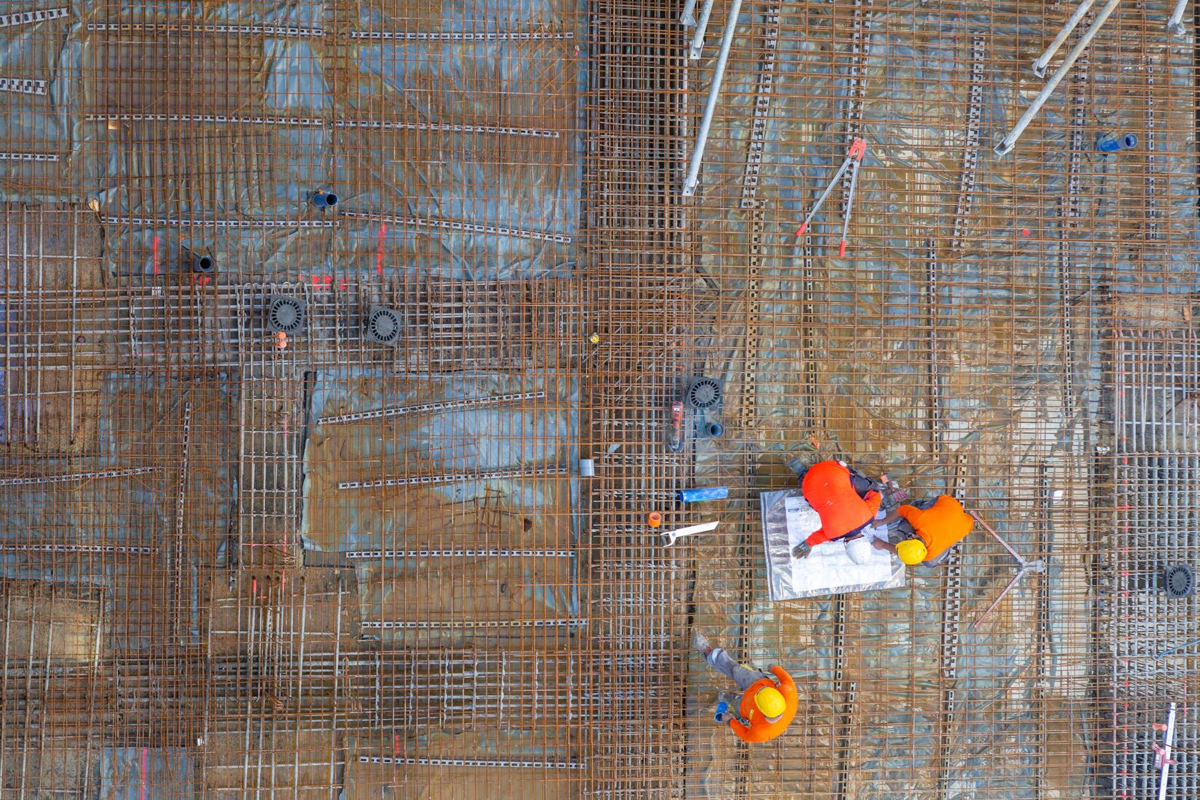 Réhabilitation lourde du siège sociale du Crédit Agricole Centre France à Clermont-Ferrand, labélisé BREEAM EXCELLENT, réalisé par le pôle Tertiaire de l'agence d'architecture SOHO ATLAS IN FINE LYON. Photo de chantier, focus sur ouvriers et plan.