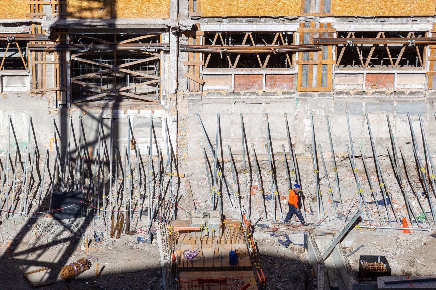 Réhabilitation lourde du siège sociale du Crédit Agricole Centre France à Clermont-Ferrand, labélisé BREEAM EXCELLENT, réalisé par le pôle Tertiaire de l'agence d'architecture SOHO ATLAS IN FINE LYON. Photo de chantier, ombre de la grue sur façade intérieure.
