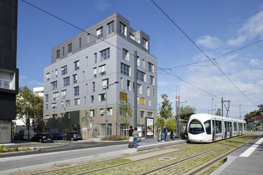 Bâtiment de bureaux et de commerce à Lyon, certifié RT2020 + BBC EFFINERGIE 2017 + BREEAM EXCELLENT, réalisé par l'agence d'architecture SOHO ATLAS IN FINE, pôle Tertiaire, agence de Lyon. Livré en 2020. Vue depuis la station de tram.